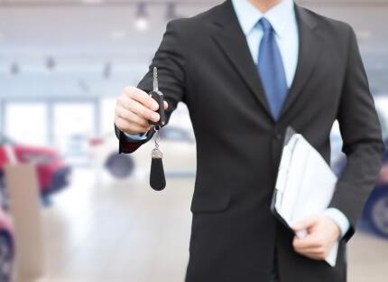 איש מכירות של חברת ליסינג מחזיק בידו מפתחות של רכב