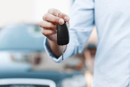 נציג מכירות של חברת טרייד אין מגיש לקונה מפתוחות של רכב