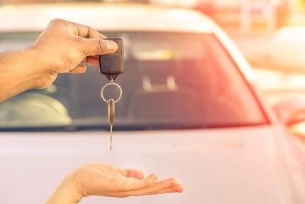 אדם מקבל מפתחות לרכב חדש שלו בטרייד אין